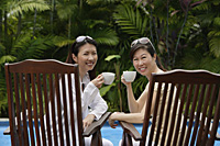 Two women sitting side by side outdoors, holding cups, turning to look at camera - Asia Images Group