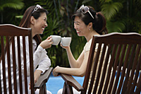 Two women sitting outdoors, toasting with cups - Asia Images Group