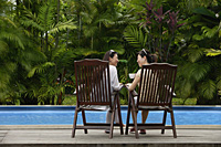 Two women sitting next to swimming pool, drinking and talking - Asia Images Group