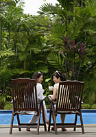 Two women sitting and talking by swimming pool - Asia Images Group