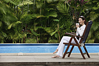 Woman sitting by swimming pool, drinking from cup, looking away - Asia Images Group