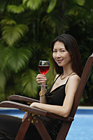 Woman sitting by swimming pool, holding a glass of wine, portrait - Asia Images Group