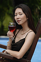Woman holding a glass of wine, swimming pool in the background, portrait - Asia Images Group