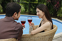 Couple sitting by swimming pool, holding wine glasses - Asia Images Group