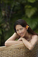Woman sitting on rattan chair, wearing flower, portrait - Asia Images Group