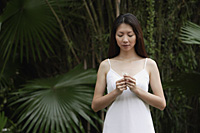 Woman in white dress, outdoors, looking at flower in her hand - Asia Images Group