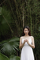 Woman in white dress, standing outdoors, looking at flower in her hand - Asia Images Group
