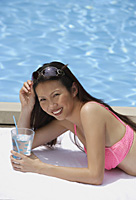 Woman in pink bikini, lying by swimming pool, holding a glass of water, smiling at camera - Asia Images Group