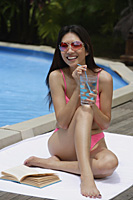 Woman in pink bikini, sitting by swimming pool, drinking from a glass of water - Asia Images Group