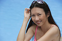 Woman by swimming pool, smiling at camera, head shot - Asia Images Group