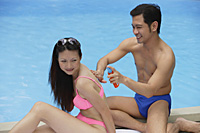 Couple by swimming pool, man applying sun tan lotion on woman - Asia Images Group