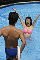 Woman in swimming pool, arms outstretched, looking at man standing in front of her - Asia Images Group