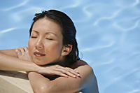 Woman leaning at the edge of swimming pool, arms crossed, eyes closed - Asia Images Group