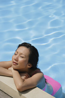 Woman leaning at the edge of swimming pool, arms crossed, eyes closed, high angle view - Asia Images Group