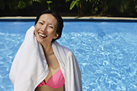 Woman wiping herself with a towel, swimming pool in the background - Asia Images Group
