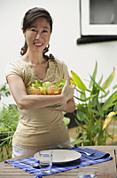 Woman standing at outdoor table, holding bowl of salad - Asia Images Group