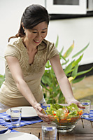 Woman setting a table for a meal, putting bowl of salad on the table - Asia Images Group