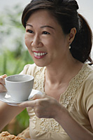 Woman with cup and saucer, having a drink, smiling - Asia Images Group