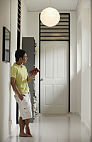 Man standing in hallway at home, holding a book, looking away - Asia Images Group