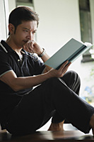 Man reading a book, serious expression - Asia Images Group