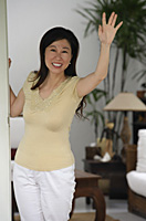 Woman standing at doorway of house, waving - Asia Images Group