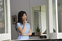 Woman at home, standing by window, looking out, hand on chin - Asia Images Group