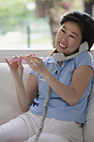 Woman filing her nails and talking on telephone - Asia Images Group