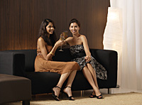 Two girls sitting on couch holding champagne, toasting, smiling at camera - Asia Images Group