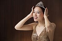 woman wearing crown, hands on crown on head, smiling at camera - Asia Images Group