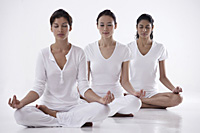 three women sitting in yoga posture OM, meditating, eyes closed - Asia Images Group