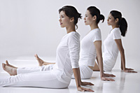 three women of mixed race sitting with legs outstretched, side view - Asia Images Group