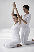 two women practicing yoga postures, teaching - Asia Images Group