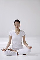 Woman sitting cross legged on floor, meditating, eyes closed - Asia Images Group