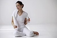 Woman sitting on floor with towel and water bottle, relaxing - Asia Images Group