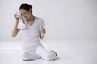 Woman sitting on floor with water bottle and towel, drying off sweat on face - Asia Images Group