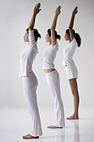 Three women standing in yoga posture mountain, arms overhead in prayer - Asia Images Group