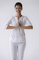 Woman standing with hands in namaste, prayer, smiling, looking at camera - Asia Images Group