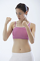Woman standing in fighting stance, boxing - Asia Images Group