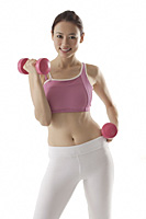 Woman lifting weights, looking at camera, smiling - Asia Images Group