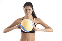 Woman holding volleyball, getting ready to pass ball, playing sports - Asia Images Group