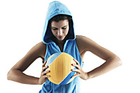 Woman holding volley ball, looking at ball, wearing hood, sports - Asia Images Group