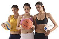 three women of different race, holding volleyball, basketball, and rugby ball, looking at camera - Asia Images Group