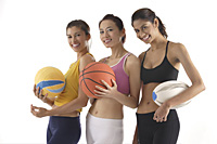 three women of different race, holding volleyball, basketball, and rugby ball, looking at camera smiling - Asia Images Group