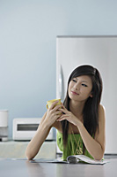 woman sitting in kitchen with magazine holding mug - Asia Images Group