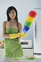 woman in kitchen, holding feather duster, thinking, cleaning - Asia Images Group