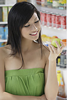 woman holding apple in front of open refrigerator - Asia Images Group