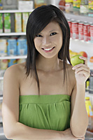 woman holding apple in front of open refrigerator, smiling, looking at camera - Asia Images Group