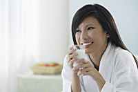 woman holding glass of milk, smiling - Asia Images Group