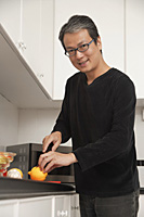 Man in kitchen cutting lemon, looking at camera and smiling - Asia Images Group