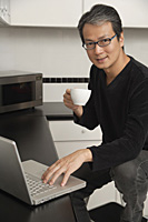 Man in kitchen with laptop / computer, looking at camera, sitting on stool, smiling and holding coffee cup. - Asia Images Group